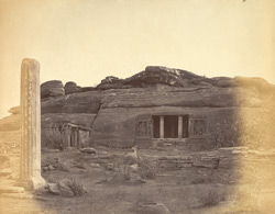 Entrance to Brahmanical Cave Temple, view from the hill in front, with monolithic pillar in foreground, Aihole, Bijapur